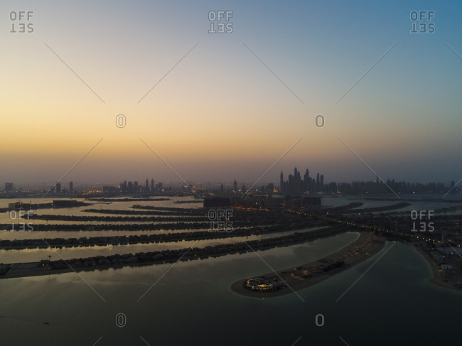 Aerial view of The Palm Jumeirah with Dubai Skyscrapers in the background at sunset, United Arab Emirates.