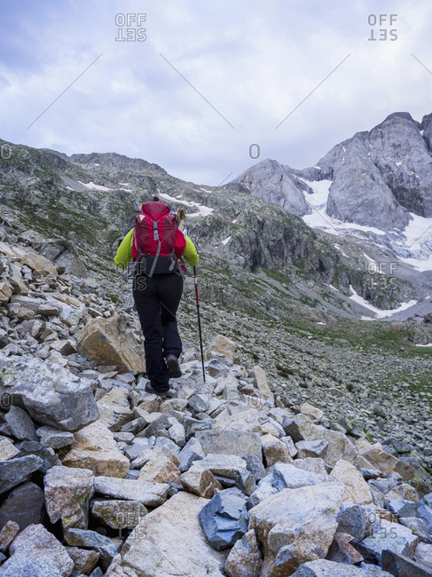 Woman hiking in the High Pyrenees ascending to mount Vignemale, Cauterets, France
