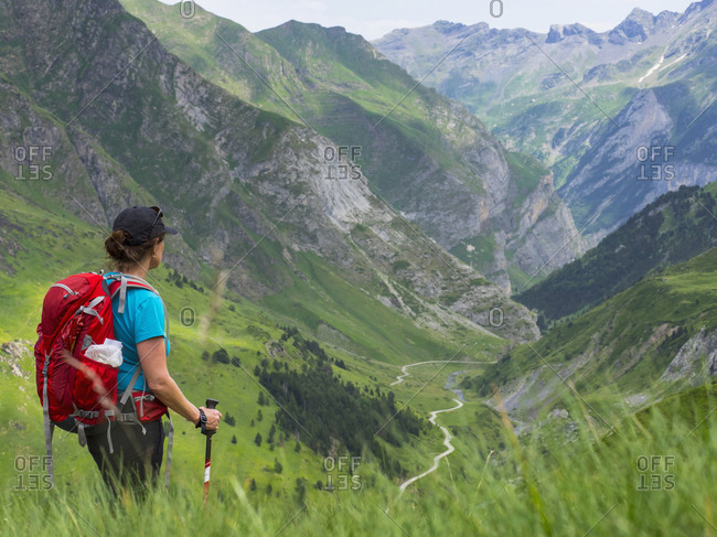Woman hiking in the High Pyrenees descending Oulettes d\'Ossoue towards Gavarnie, France