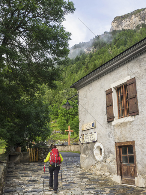 Woman hiker passing by an old building in the village of Gavarnie, France