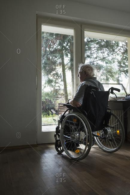 Senior man in wheelchair looking out through window