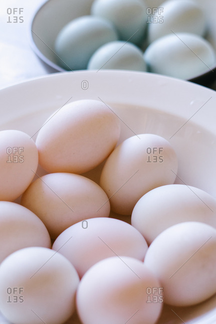 Two bowls filled with many fresh eggs