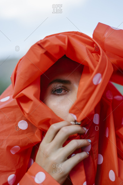 Close up of a woman looking through hole in a red polka dot raincoat