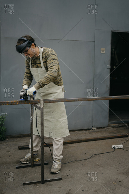 Man using tool to clean rust from metal