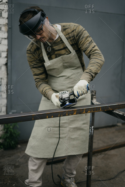Man using grinder to clean rust from metal