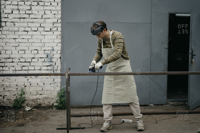 Worker using grinder to clean rust from metal