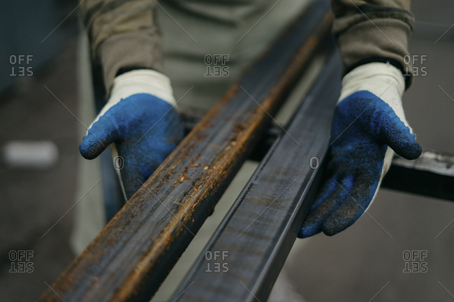 Close up worker comparing rusty and non-rusty metal bars