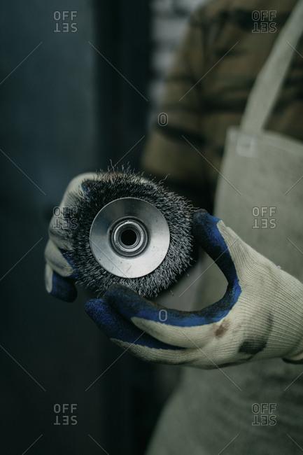 Worker holding wire brush grinder