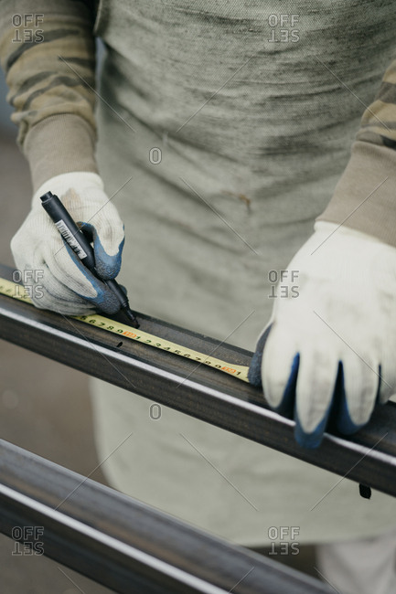 Man using tape measure and marker to mark lines on a metal bar