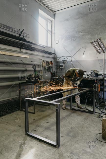 Worker grinding metal in a workshop