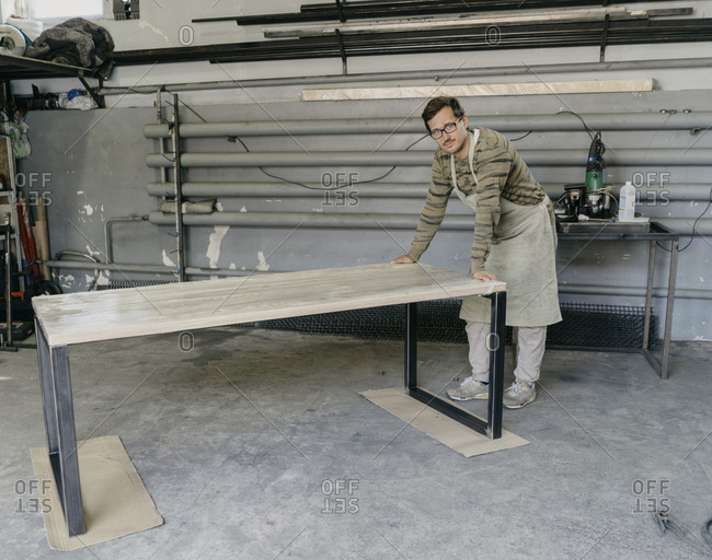 Man leaning on finished table in a workshop