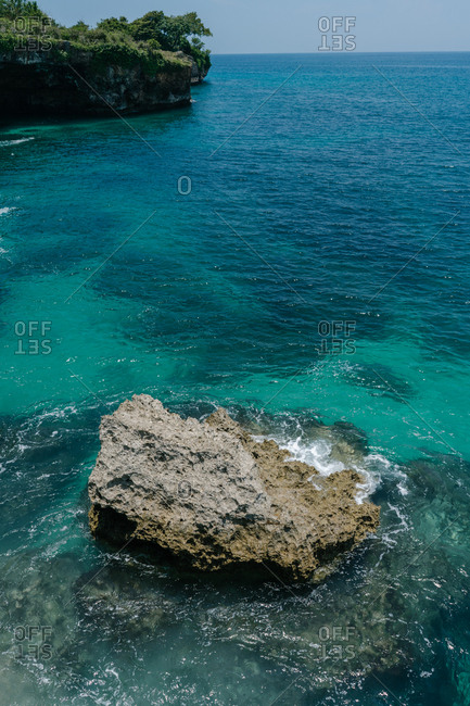 Rock formation in turquoise waters on the coast of Bali, Indonesia