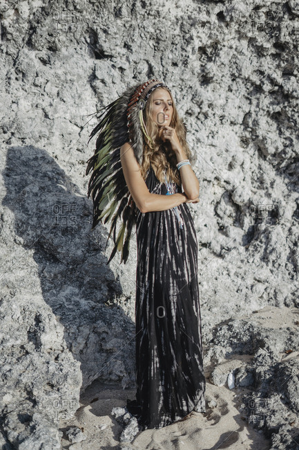 Young woman wearing feather headdress standing on rocky cliff