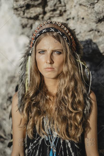 Woman wearing feather headdress standing on rocky beach