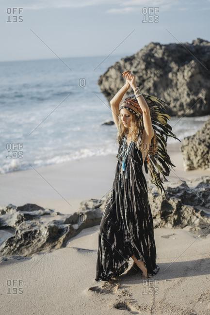 Woman wearing feather headdress walking on beach