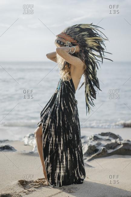 Young woman wearing feather headdress walking on beach