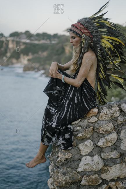 Woman wearing feather headdress sitting on rocky cliff