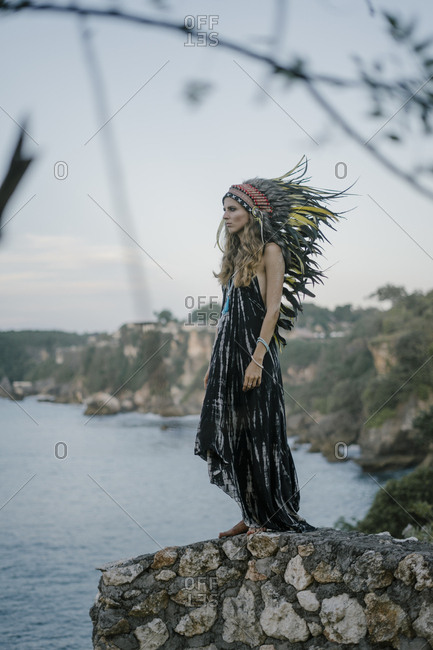 Woman wearing feather headdress standing on rocky cliff