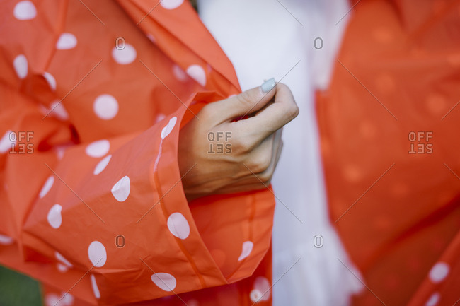 Close up of a woman wearing a red polka dot raincoat