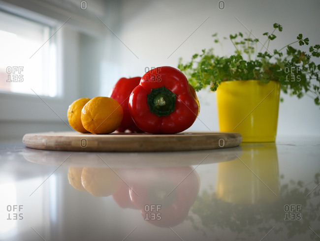 Red bell peppers and lemons on wooden cutting board