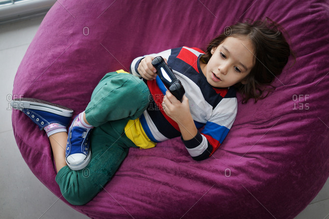 Reclining boy playing with video game console