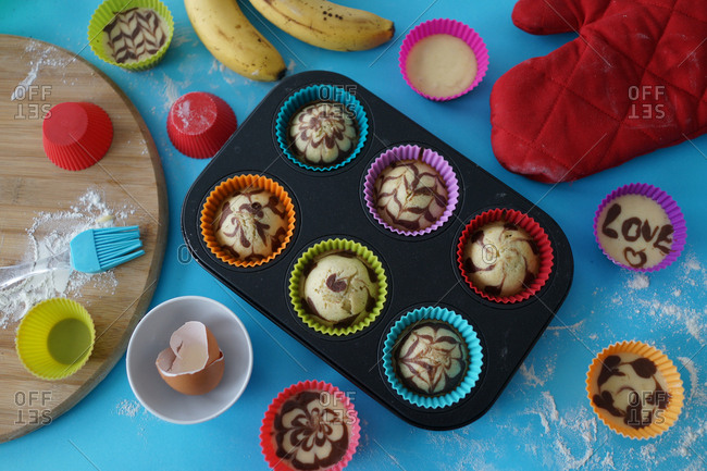 Freshly baked cupcakes with chocolate designs in muffin tin