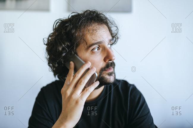 Portrait of bearded man looking away talking on phone
