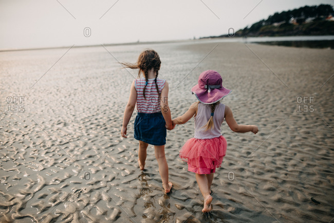 Young girl leads little sister on walk along beach at low tide