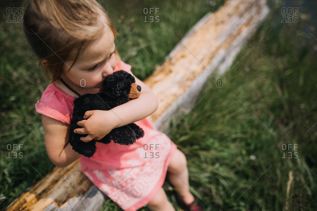 High angle view of little girl sitting on log hugging plush toy