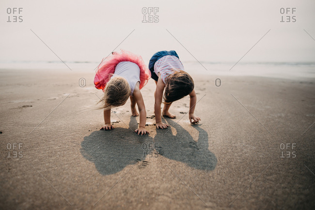Young girls walking on hands and feet at low tide at beach