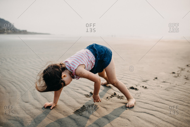 Little girl on hands and feet scratching at sand at low tide at beach
