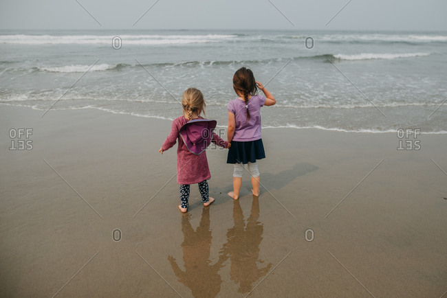 Little girl protectively holding little sister's hand standing at waters edge at beach