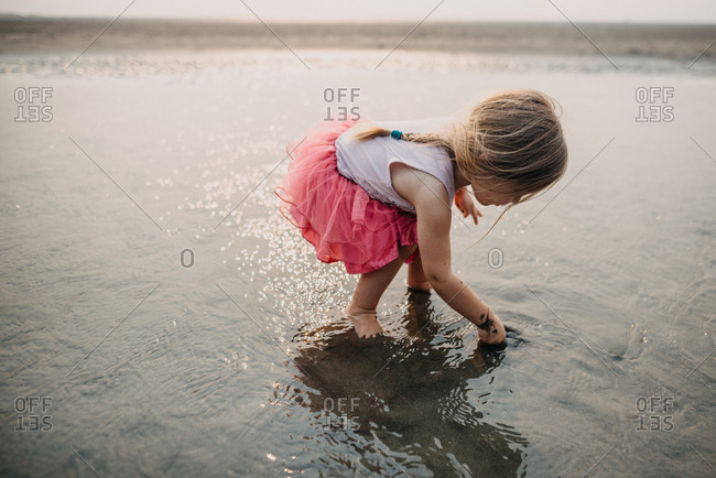 Little girl exploring tide pool in ankle deep water at seaside
