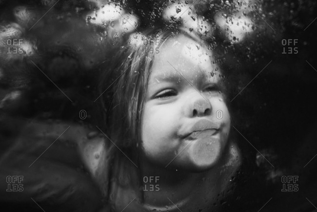 Little girl pressing lips against car window on rainy day