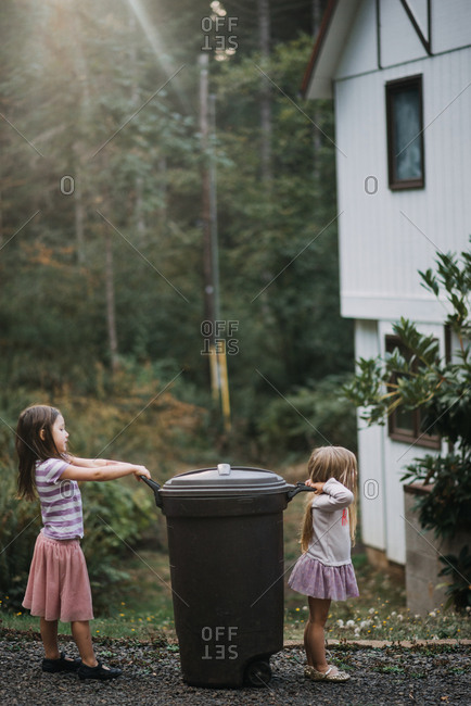 Young girl and little sister teaming up to take out garbage can