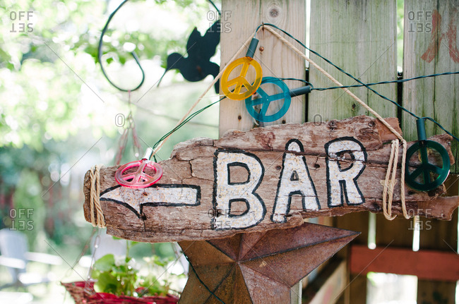 Hand made driftwood sign pointing way to bar