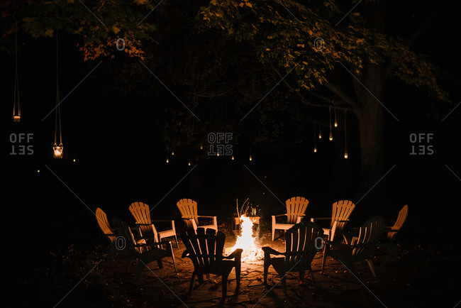Loungers arranged around a campfire in a clearing in the woods at night
