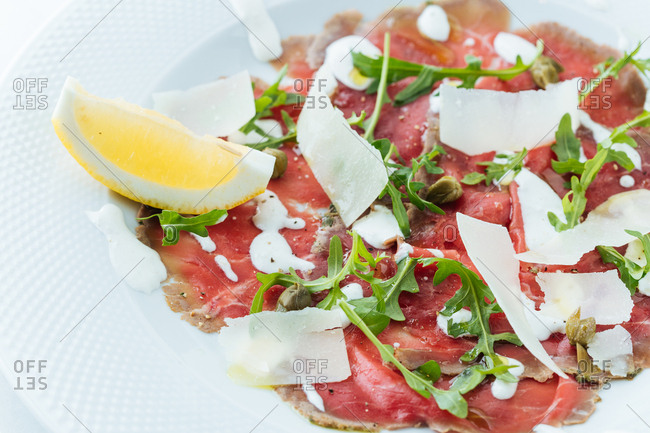 Close up of prosciutto topped with cheese, arugula and garnished with a lemon