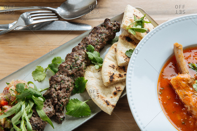 Close up of a meat kabob with salsa and pita bread served with soup