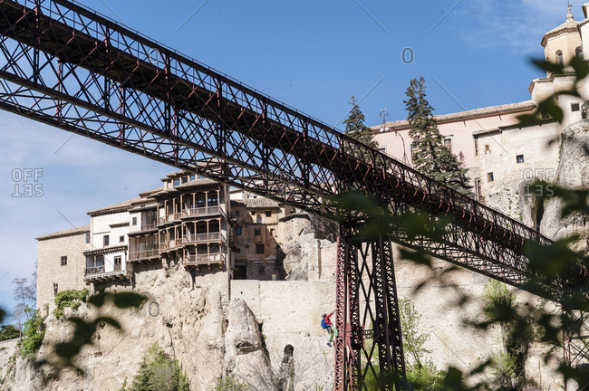 Urban climber hanging from a bridge doing a risky activity on Puente de San Lucas in Cuenca, Spain