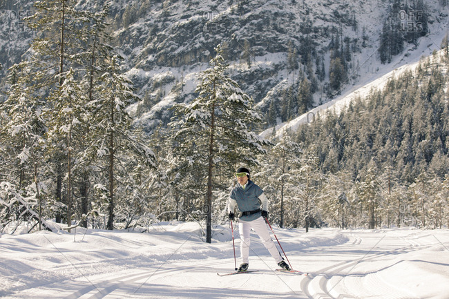 Woman cross-country skiing on scenic trail through forest