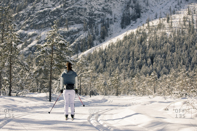 Woman cross-country skiing on groomed trail in the mountains