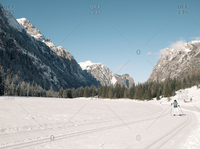 Woman cross-country skiing through scenic mountain wilderness area