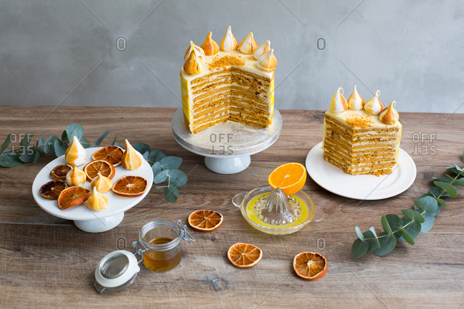Generous slice of Russian honey cake topped with mini meringues and arranged with sliced dried oranges