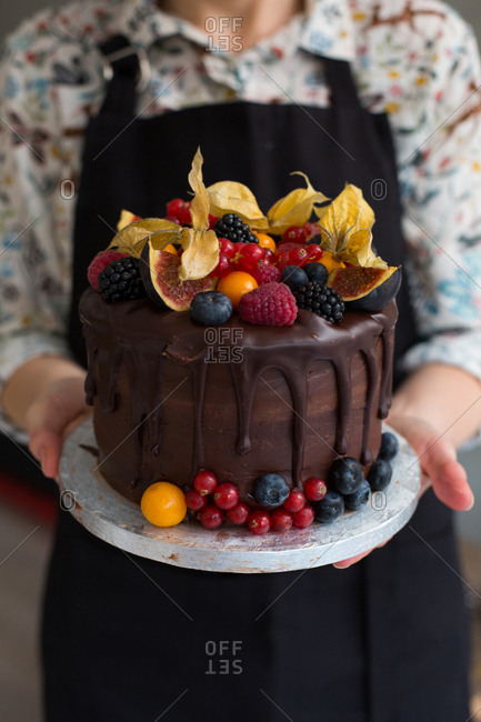 Baker presenting incredibly decadent chocolate sponge cake topped with fruits of the forest