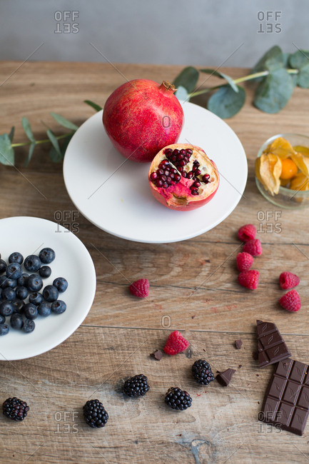 High angle view of arrangement of variety of berries and broken slab of chocolate