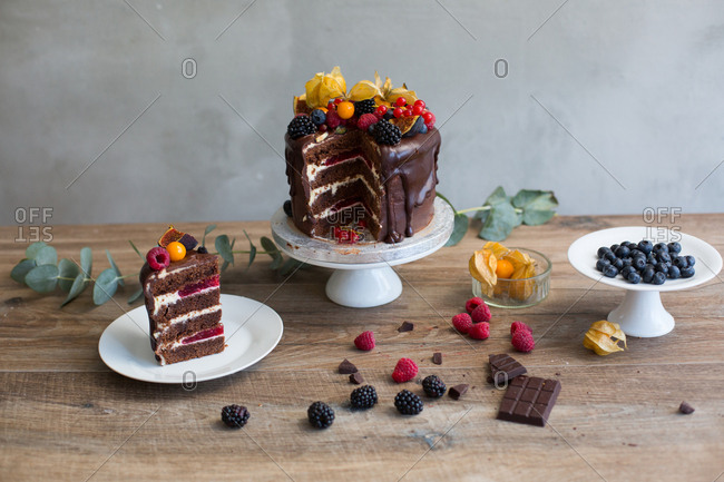 High angle view of sliced chocolate sponge cake filled with raspberry compote and topped with variety of berries