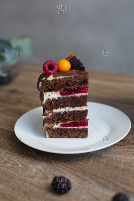 Generous slice of chocolate sponge cake filled with raspberry compote and topped with variety of berries