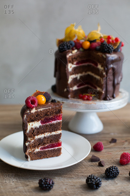 Sliced chocolate sponge cake filled with raspberry compote and topped with variety of berries