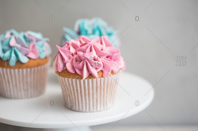 Close up of trio of cupcakes with pink and blue frosting